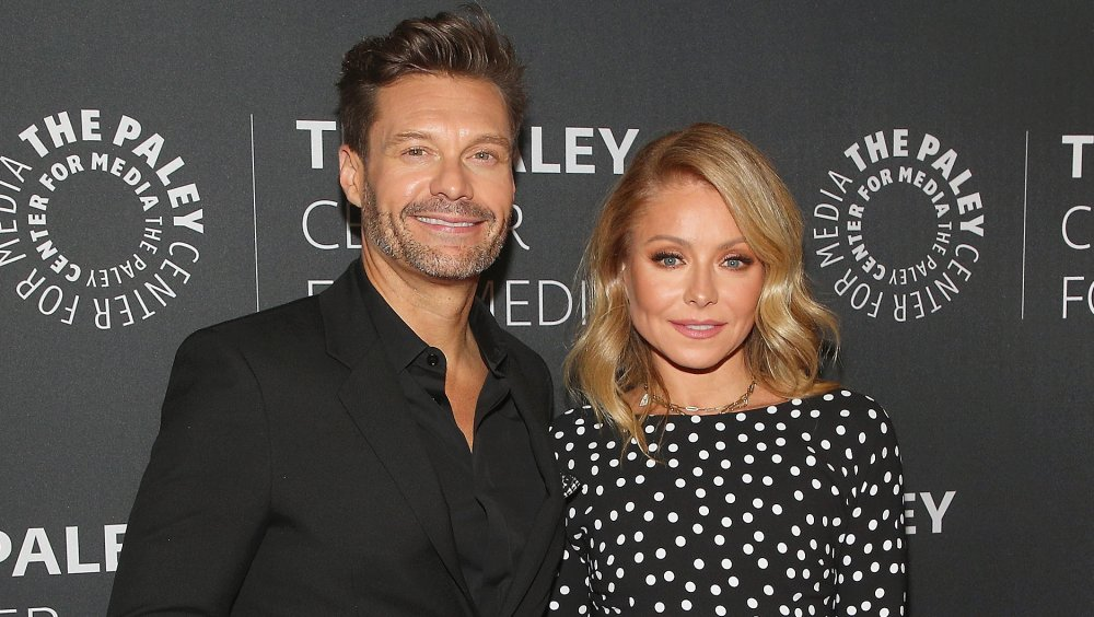 Ryan Seacrest and Kelly Ripa smiling while posing arm in arm