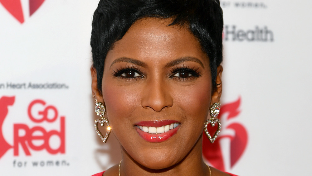 Tamron Hall smiling at a red carpet event