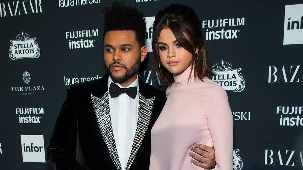 The Weeknd in a black velvet suit and bow tie, Selena Gomez in a pink dress, posing together on the red carpet