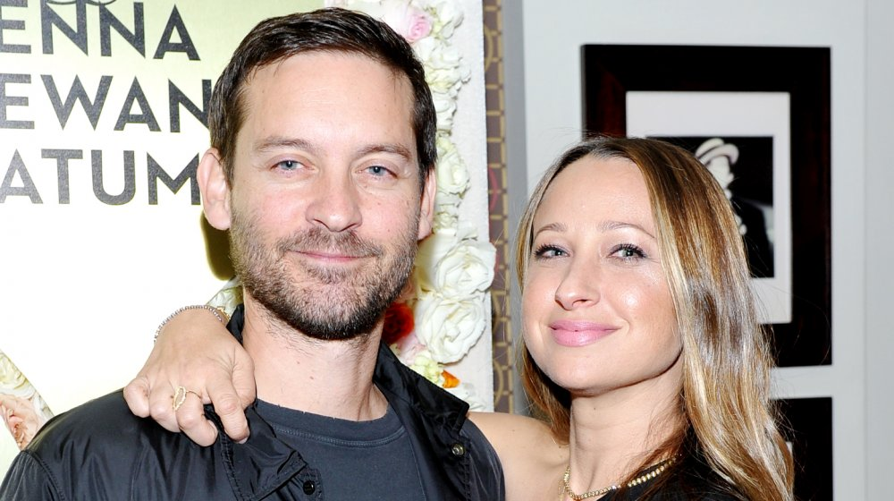 Tobey Maguire and Jennifer Meyer smiling while posing arm in arm