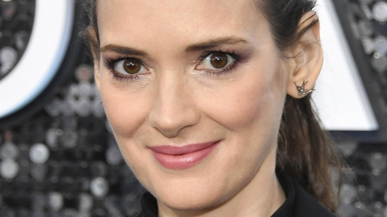 Winona Ryder smiling at camera in pink lipstick