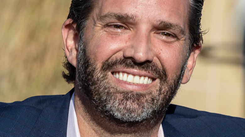 Donald Trump, Jr. smiling and looking to the side