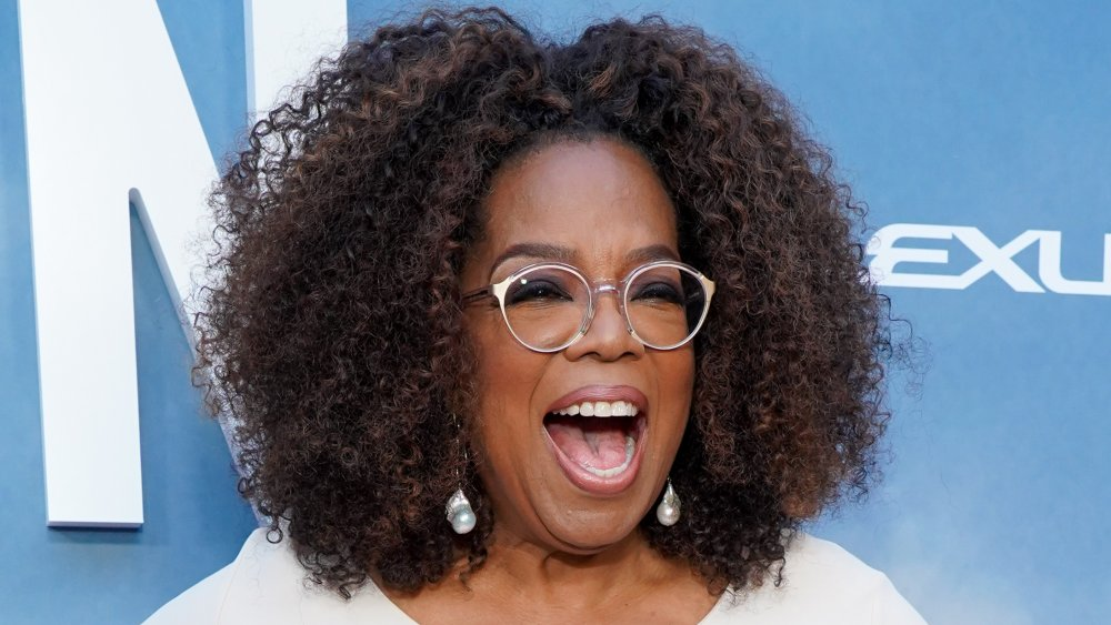 Oprah Winfrey in a white outfit, laughing on the red carpet