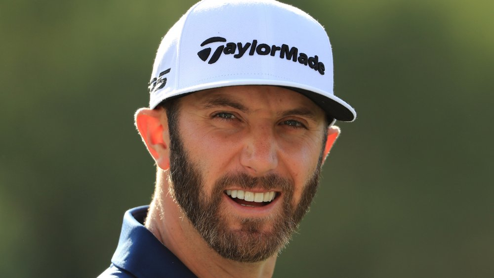 Dustin Johnson in a white cap, smiling during a match
