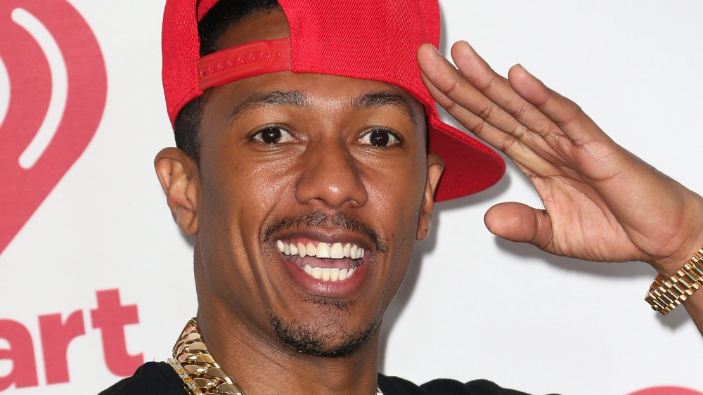 Nick Cannon saluting, wearing a red hat turned to the side