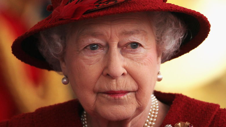 Queen Elizabeth looking stern in a hat and pearls
