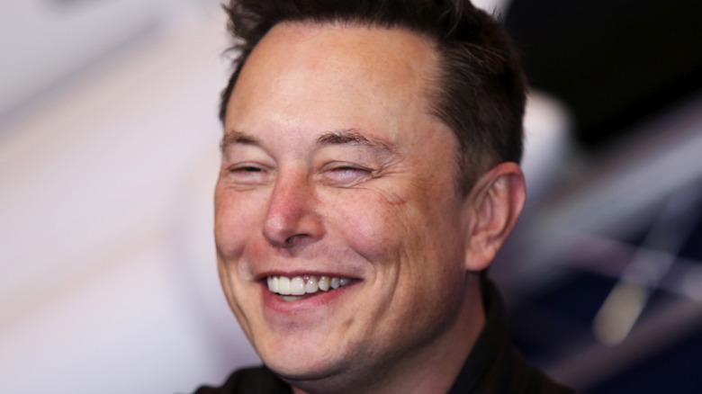 Elon Musk smiles at an event