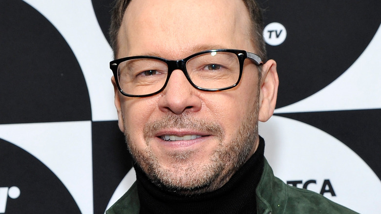 Donnie Wahlberg poses in black-framed glasses.