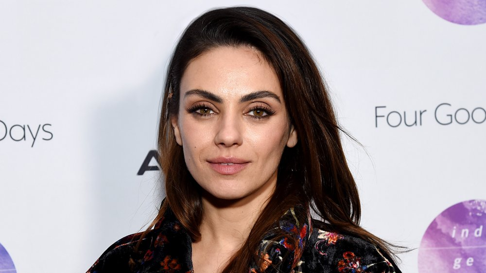 Mila Kunis in a black printed top, with a small smile, posing at an event