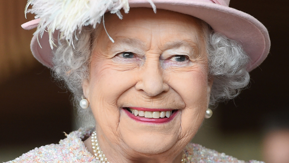 Queen Elizabeth II smiling at an event while wearing light pink