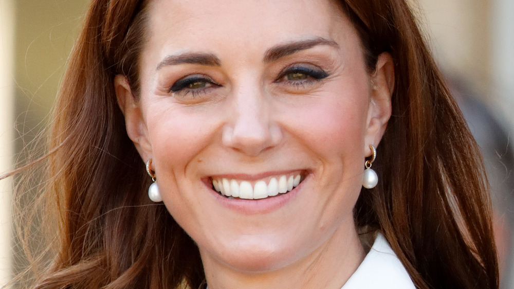 Kate Middleton smiling while wearing pearl earrings