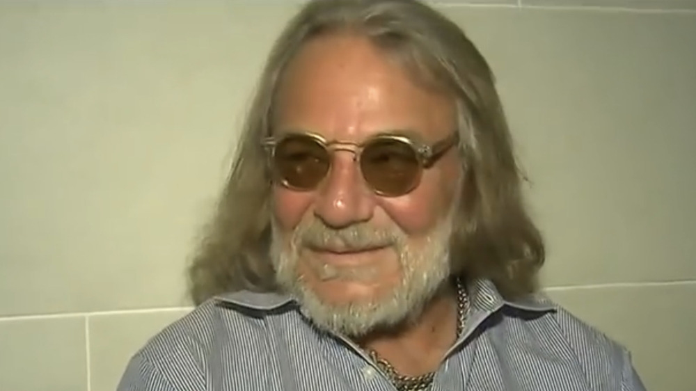 Dr. Harold Bornstein wearing shaded glasses and smiling to his right