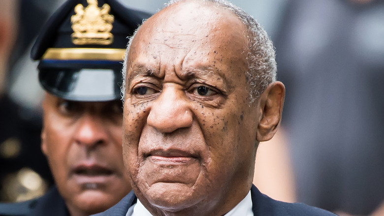 Bill Cosby flanked by police