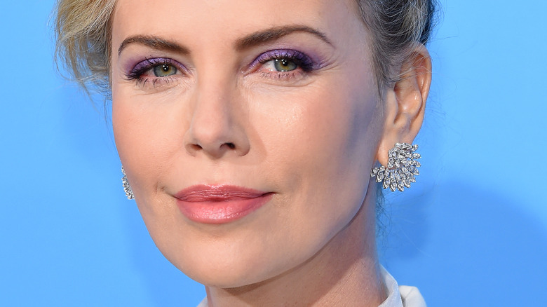 Charlize Theron smiles in purple eyeshadow