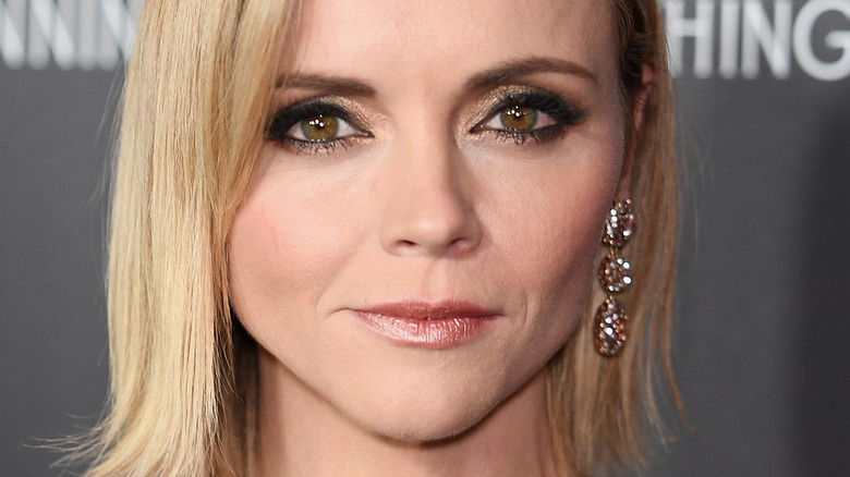 Christina Ricci poses in a black dress and blonde hair