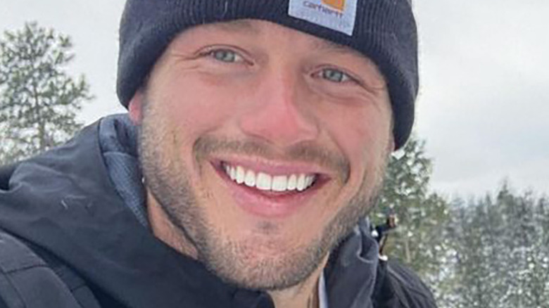 Colton Underwood smiling and wearing a winter hat