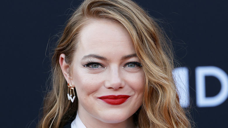 Emma Stone smiles while wearing red lipstick