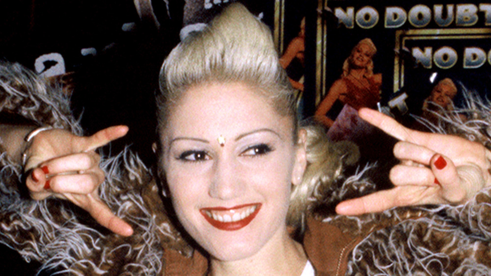 Gwen Stefani smiling while throwing up a rock on sign