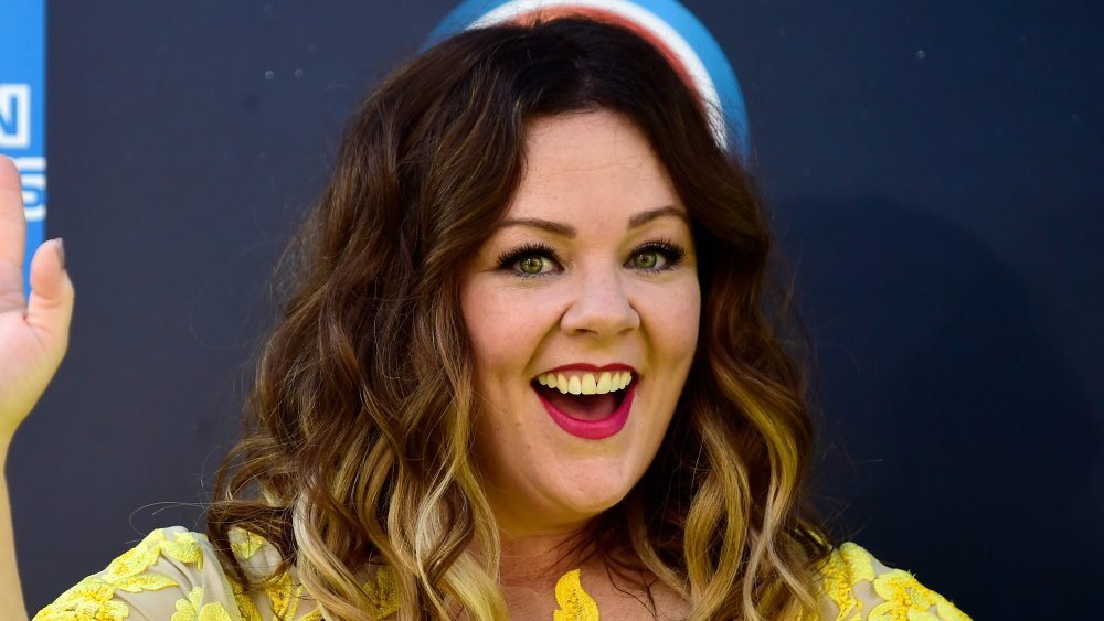 Melissa McCarthy in a yellow dress, smiling big and waving