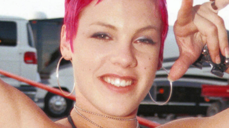 Pink smiling with bright pink hair at age 21