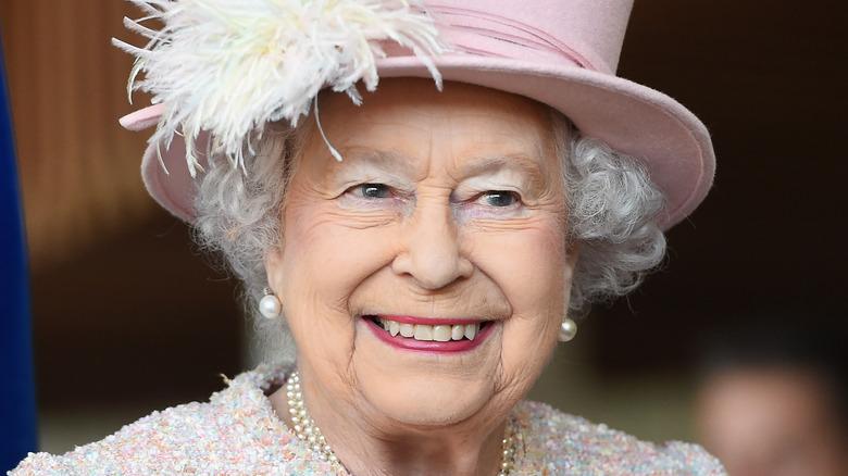 Queen Elizabeth smiles in pink hat.