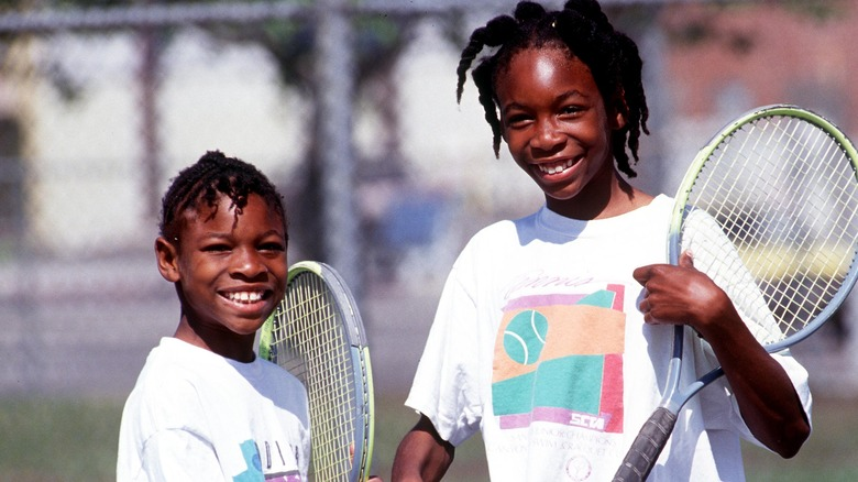 Serena Williams with big sister Venus Williams in 1991, holding rackets on a tennis court