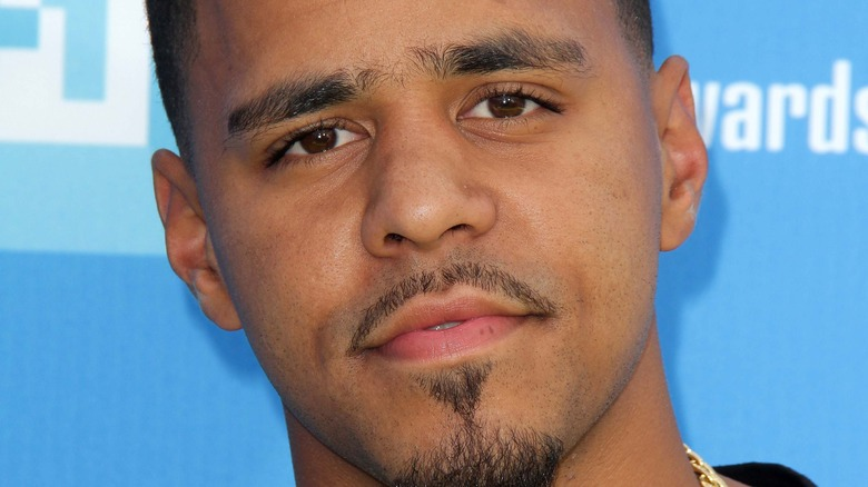 J. Cole gives a slight smile on the red carpet