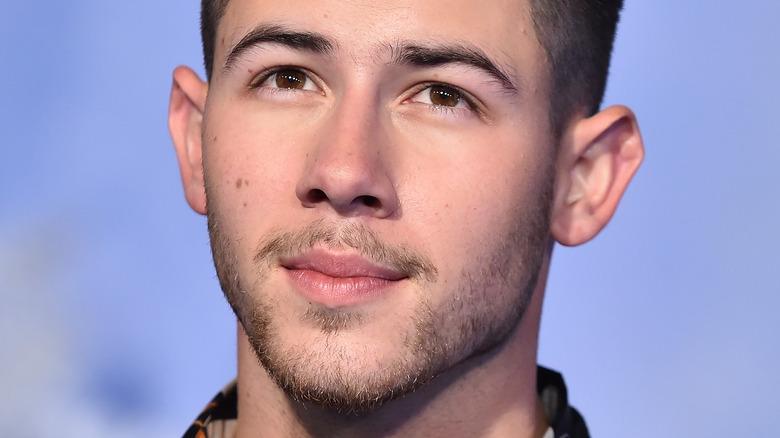 Nick Jonas slightly smiling