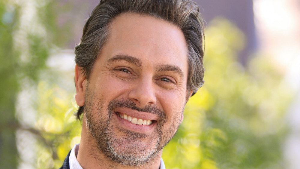 Thomas Sadoski, smiling, outside, in a collared shirt, facial hair