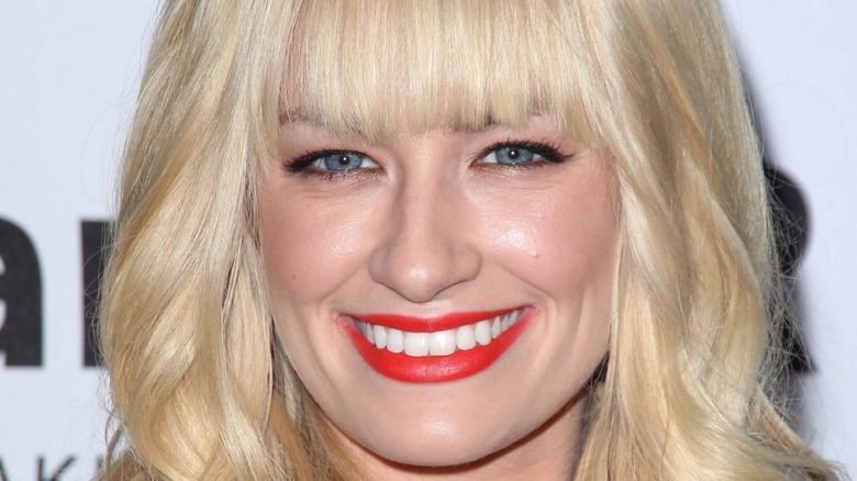 Beth Behrs with wide smile and red lipstick