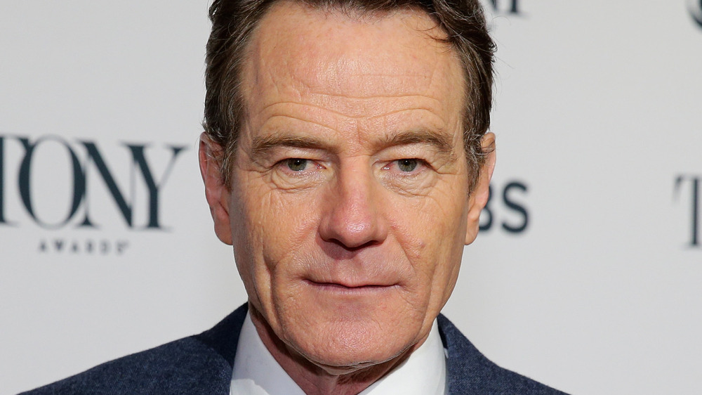 Bryan Cranston poses in a navy suit.