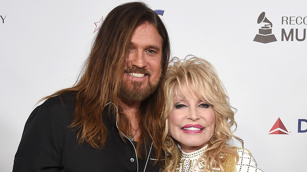 Billy Ray Cyrus and Dolly Parton embracing on the red carpet