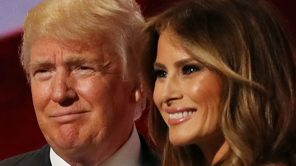 Donald Trump and Melania Trump smiling on stage