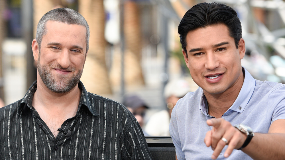 Dustin Diamond and Mario Lopez sitting down and talking on couch with Lopez pointing