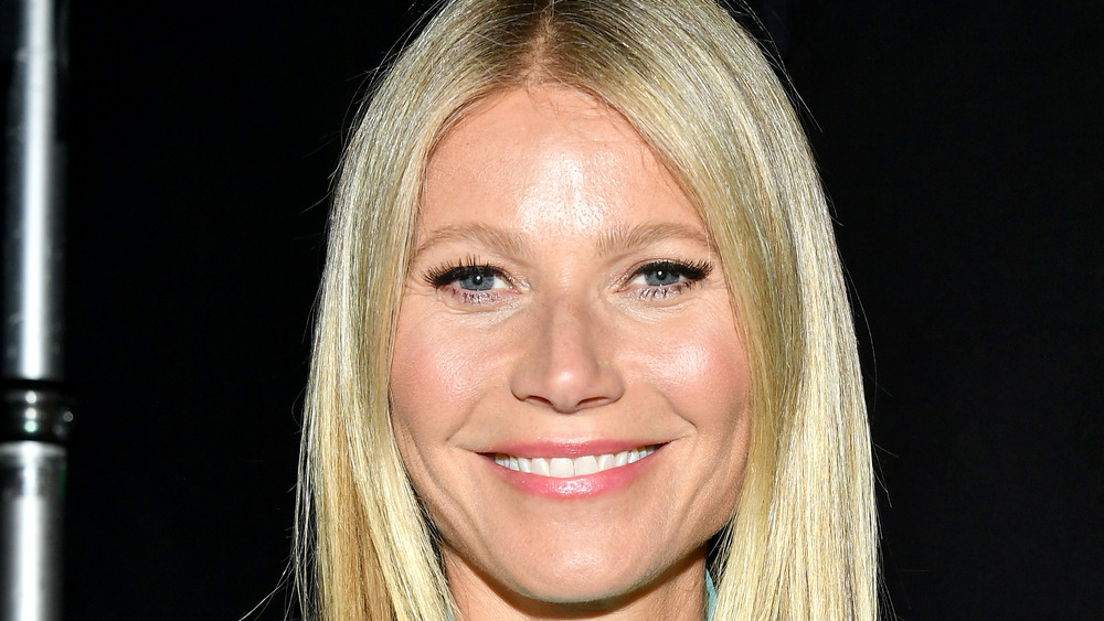Gwyneth Paltrow smiling wide with her hair parted down the middle