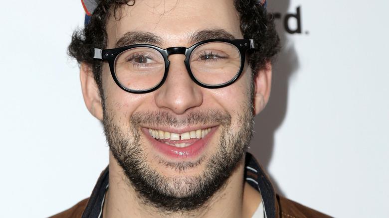Jack Antonoff smiling and wearing glasses