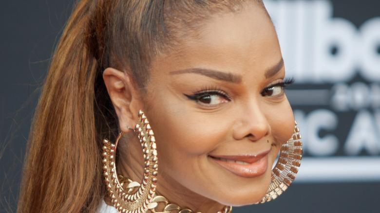 Janet Jackson smiling over shoulder
