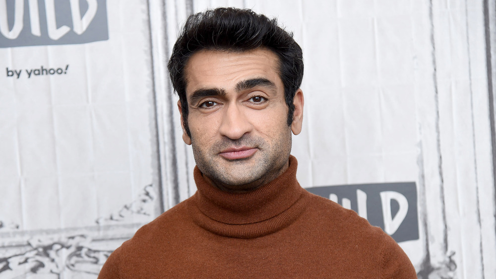 Kumail Nanjiani slightly smiling on the red carpet in a brown turtleneck sweater