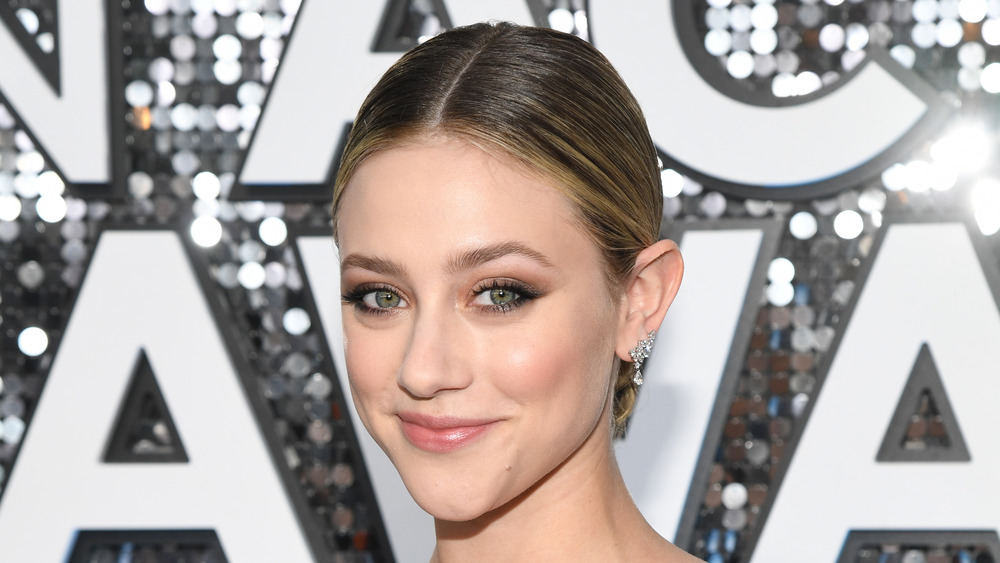 Lili Reinhart smiles for cameras with her hair in a low bun