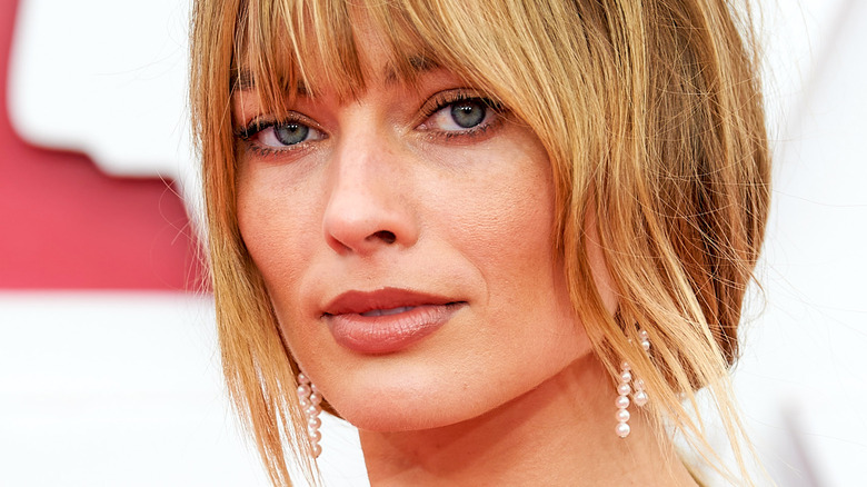 Margot Robbie with bangs and slight smile