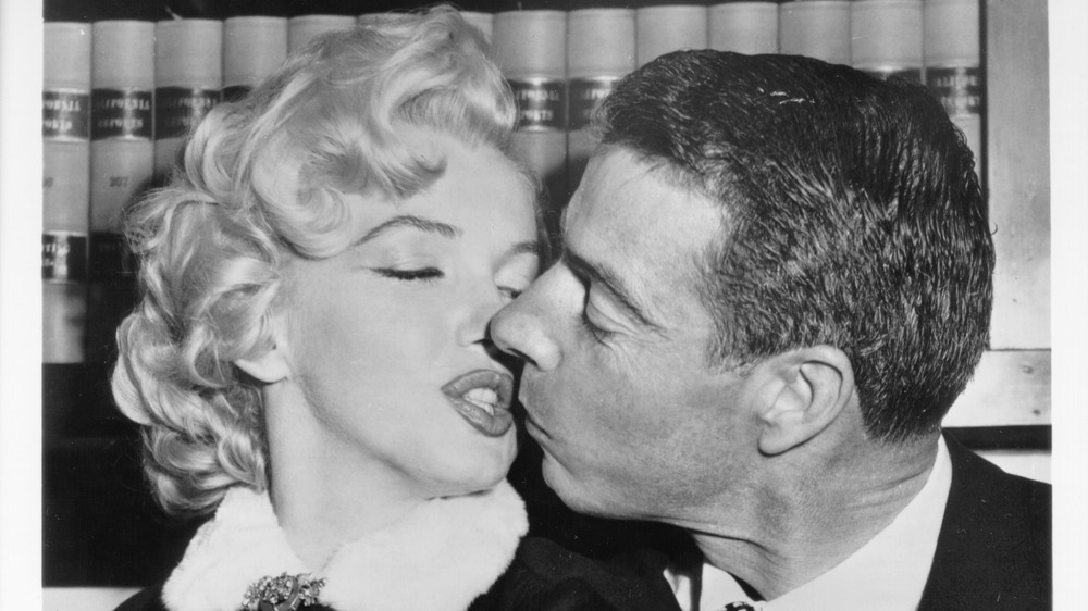 Marilyn Monroe and Joe DiMaggio kissing