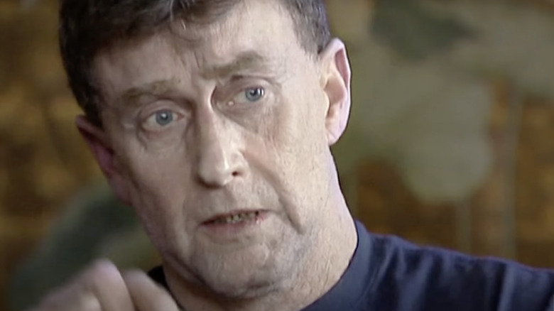 Michael Peterson tears up while half-smiling.