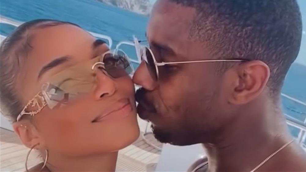 Michael B. Jordan kissing Lori Harvey on the cheek on a yacht