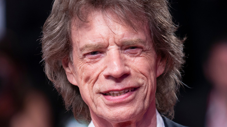 Mick Jagger smiles in a dark suit.