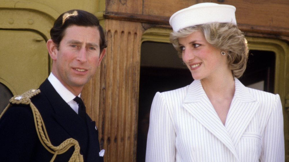Prince Charles looking straight ahead as Princess Diana smiles at him