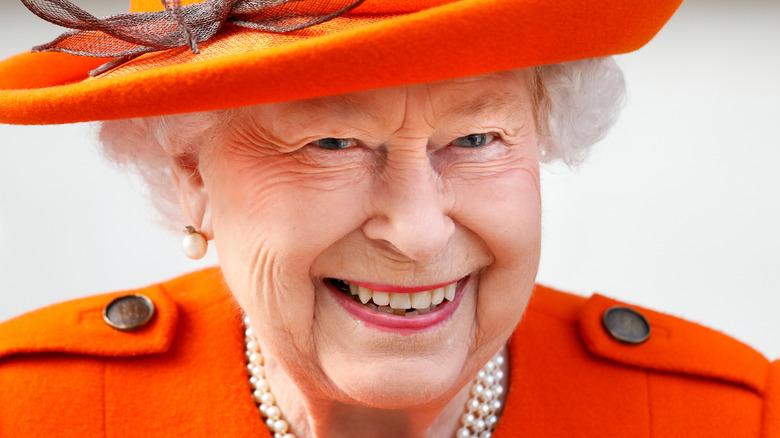 smiling Queen Elizabeth II dressed in orange