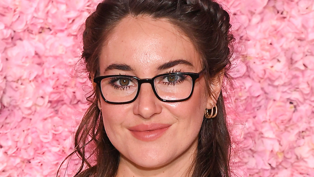 Shailene Woodley standing against a wall of pink roses wearing glasses