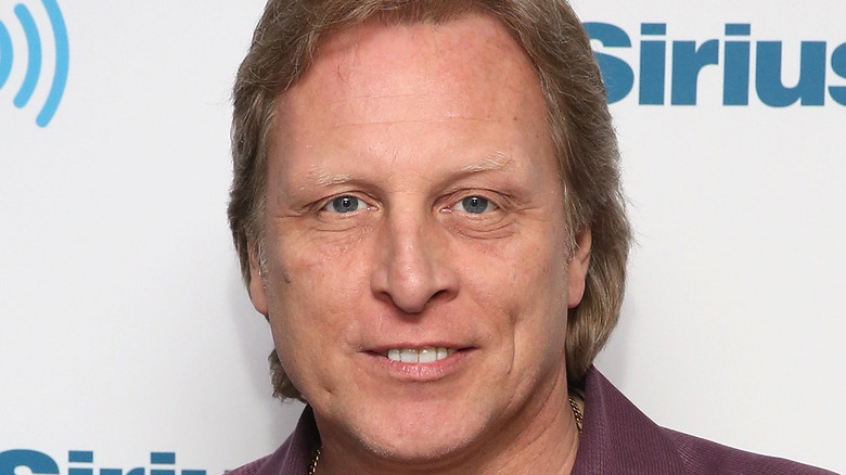 Sig Hansen smiles in front of a photo wall at a radio show