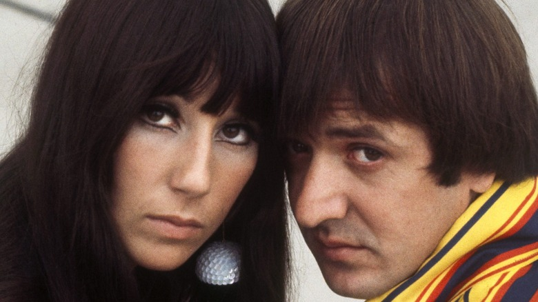 Sonny and Cher resting their heads against one another