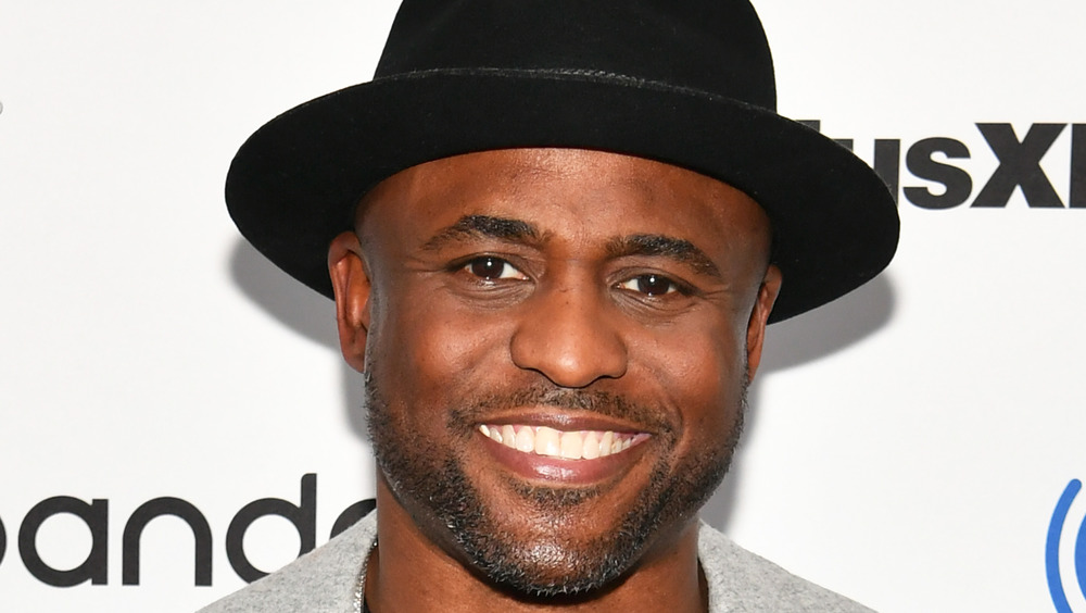 Wayne Brady wears a black fedora hat and smiles at the camera